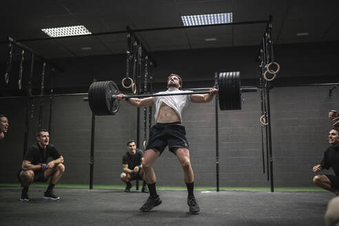 People cheering man lifting barbell while standing in gym - SNF00560