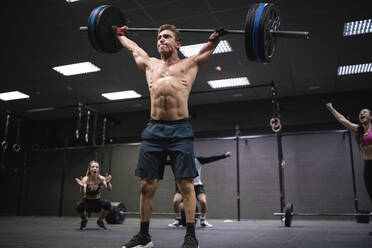 Amputee athlete picking barbell with people cheering in background at gym - SNF00563