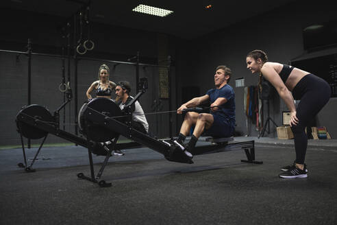 Athletes exercising with rowing machine at gym - SNF00566