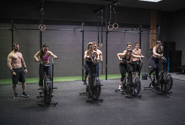 Women exercising on fitness bike with men standing behind at gym - SNF00569