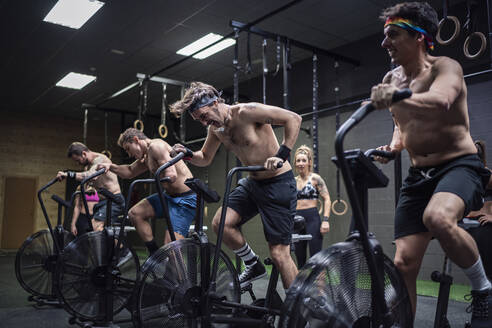 Men exercising on fitness bike with women standing in background at gym - SNF00572