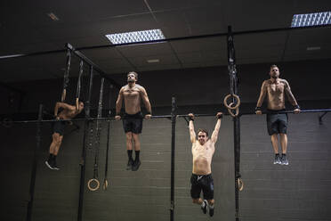 Athletes doing pull ups exercise on rod at gym - SNF00575