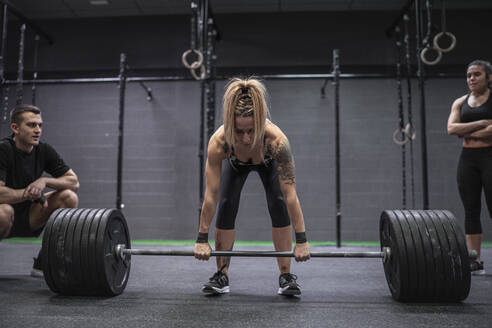 Athletes watching woman picking barbell while standing in gym - SNF00584