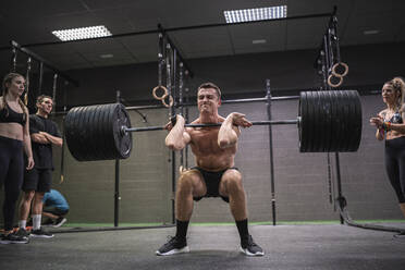 Athletes cheering man crouching while picking barbell up at gym - SNF00587