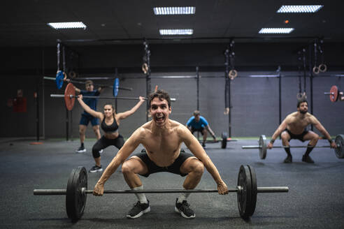 Athletes picking barbell while exercising at gym - SNF00590