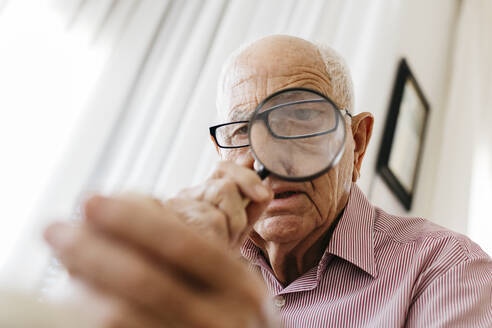 Retired senior male looking through magnifying glass at fossil - JRFF04763