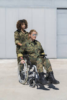 Young female military soldier pushing colleague on wheelchair at army base during sunny day - MTBF00664
