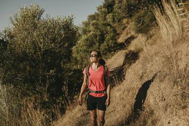 Smiling woman trekking on mountain at Sierra De Hornachuelos, Cordoba, Spain - DMGF00161