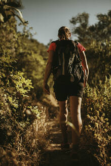 Woman with backpack trekking on path of mountain at Sierra De Hornachuelos, Cordoba, Spain - DMGF00176