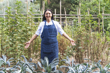 Smiling mature woman with arms outstretched standing by fresh organic kale plants at vegetable garden - FMOF01195