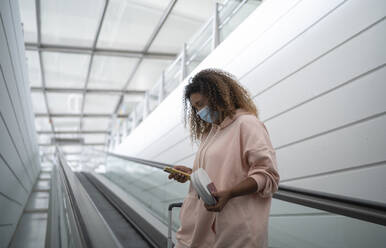 Young woman using smart phone while standing on escalator at airport - SNF00597