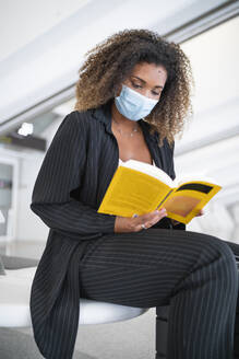 Curly hair woman reading book while wearing protective face mask sitting at airport - SNF00600