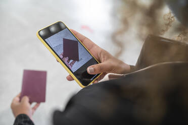 Woman taking photo of passport on smart phone while standing at airport - SNF00603