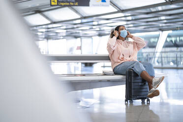 Young woman listening to music while wearing protective face mask sitting at airport - SNF00609