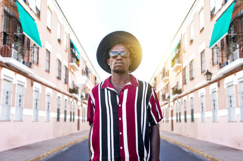 Low angle of confident young African American male in stylish stripped shirt and sunglasses with hat looking at camera while standing against blurred urban street - ADSF16181