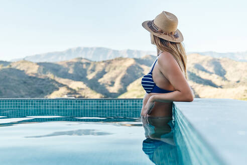 Side view of unrecognizable slim female in swimwear and hat standing in swimming pool and admiring mountainous landscape during summer vacation - ADSF16382
