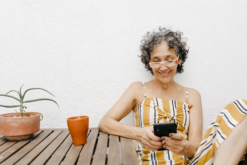 Smiling mature woman with short hair using smart phone while sitting against white wall at back yard - TCEF01197