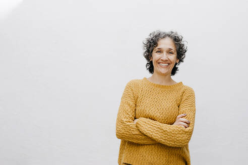 Smiling woman in orange sweater standing with arms crossed against white wall - TCEF01209