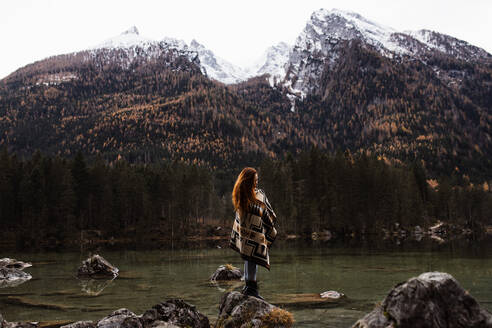 Side view of unrecognizable distant female traveler in warm outfit standing on rocky shore of lake and observing amazing scenery of autumn forest and snowy mountains in cloudy day - ADSF16425