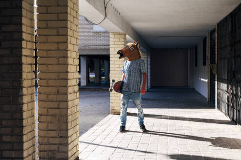 Man holding skateboard wearing horse mask while standing on footpath during sunny day - JCMF01535