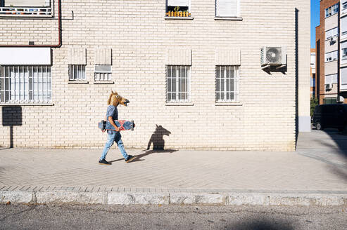 Man in horse mask walking with skateboard on footpath by building in city during sunny day - JCMF01538