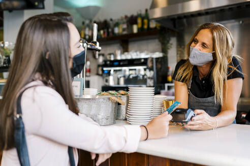 Businesswoman in face mask paying through credit card at counter in cafe during COVID-19 crisis - EGAF00898
