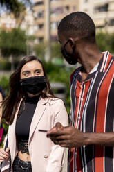Young couple wearing face masks while walking in city during COVID-19 outbreak - EGAF00925