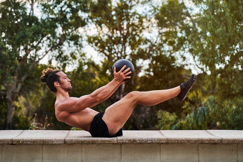 Side view of concentrated male athlete with strong naked torso balancing with medicine ball while doing abdomen exercises during training in park - ADSF16508