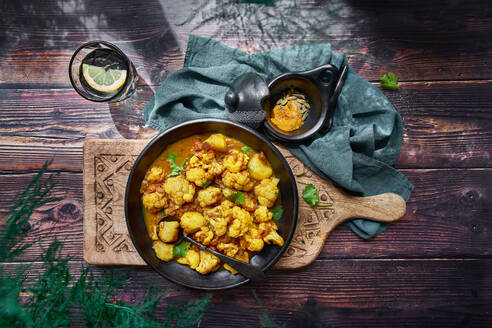 Top view of delicious cauliflower stew with turmeric and vegetables served on wooden table for dinner - ADSF16529
