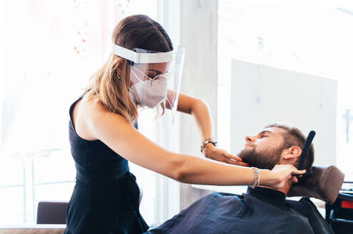 Barber woman in protective mask and face shield shaving male with sharp straight razor while working in barbershop during coronavirus outbreak - ADSF16541