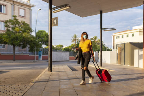 Young woman wearing protective mask while walking with luggage at bus stop - JPTF00587
