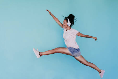 Excited beautiful woman listening music through headphones while jumping against turquoise background - EBBF00805