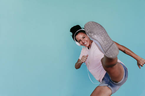 Excited woman kicking while listening music through headphones against turquoise background - EBBF00808