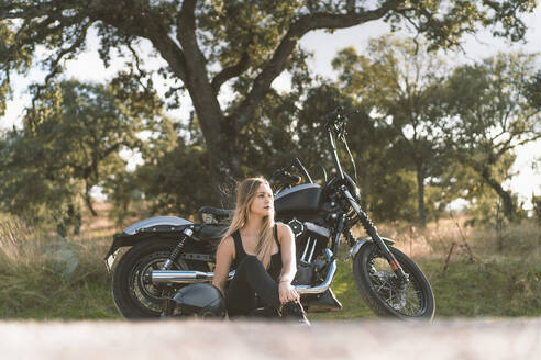 Thoughtful blond woman sitting against motorcycle on roadside - DAMF00521