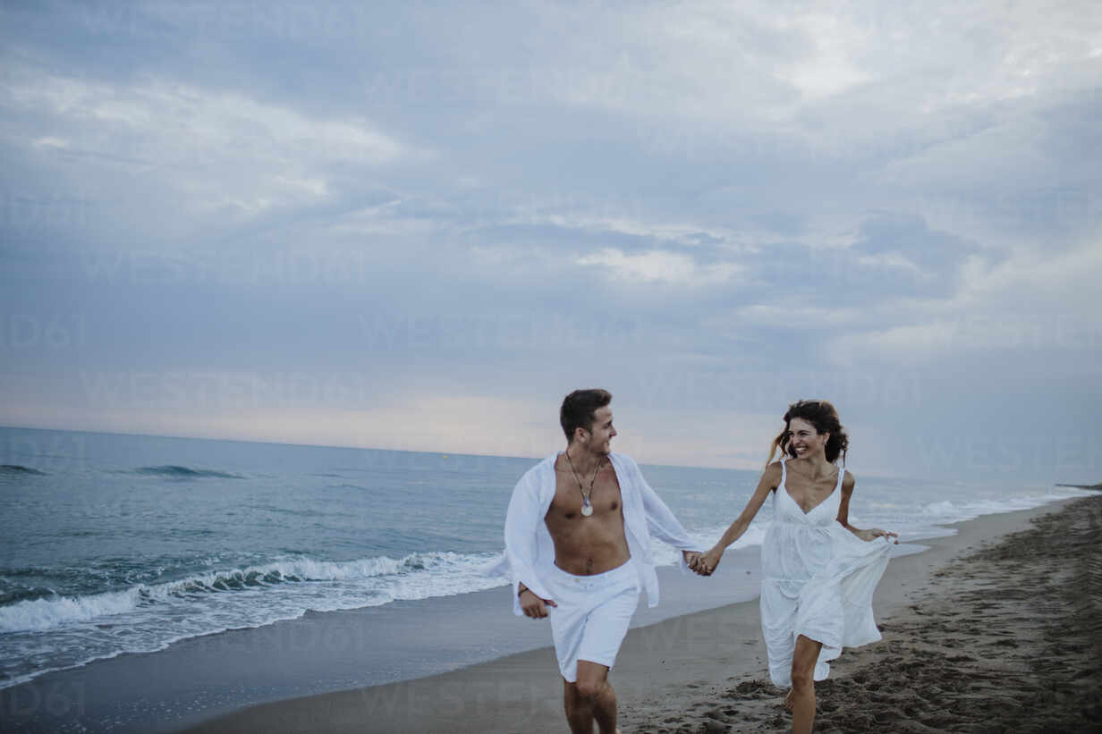Smiling couple looking at each other while running on beach - GMLF00686 - Gala Martínez López/Westend61