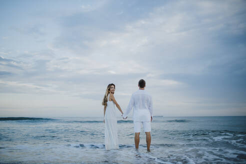 Woman looking behind while holding hand of man standing in water at beach - GMLF00689