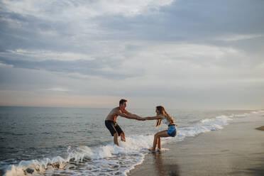 Couple enjoying while playing at beach - GMLF00701