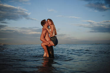 Man kissing and carrying woman while standing in water during sunset - GMLF00704