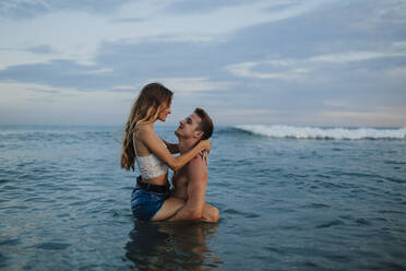 Boyfriend carrying girlfriend while standing in water at beach - GMLF00707