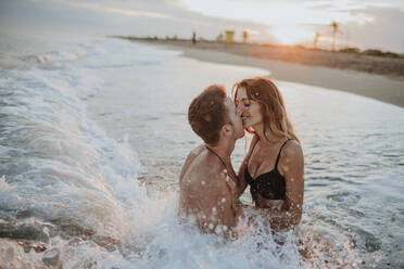 Couple doing romance while sitting in water at beach - GMLF00716