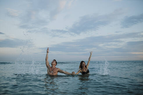 Playful couple holding hand while standing in water - GMLF00719