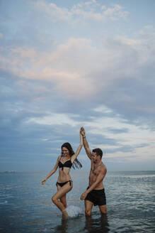 Couple in swimwear walking in water at beach - GMLF00722