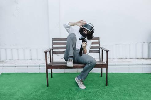 Man playing video game using virtual reality eyeglasses while sitting at backyard - MRRF00546