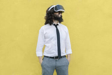 Business wearing virtual reality eyeglasses standing with hands in pockets against yellow wall - MRRF00552