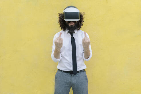 Man wearing virtual reality eyeglasses gesturing while standing against wall - MRRF00555