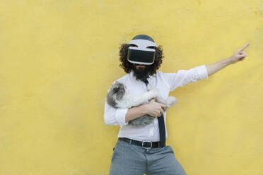 Man wearing virtual reality eyeglasses holding cat while standing against wall - MRRF00561