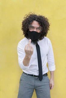 Man with face mask and eyeglasses showing hand sign while standing against wall - MRRF00570