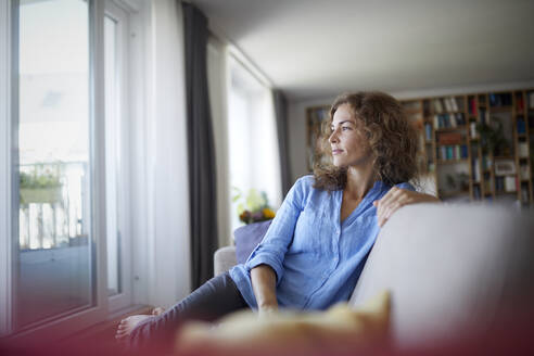 Woman looking at window while sitting on sofa at home - RBF07945