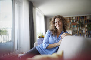 Smiling woman sitting on sofa by window at home - RBF07948