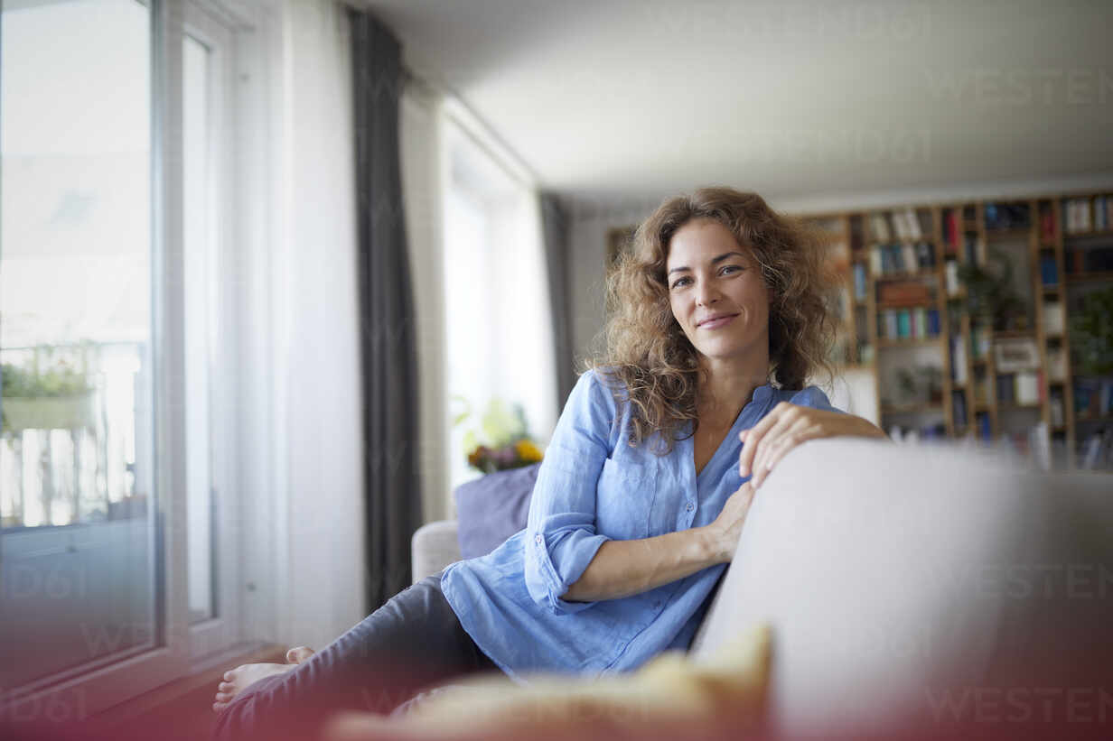 Smiling woman sitting on sofa by window at home - RBF07948 - Rainer Berg/Westend61